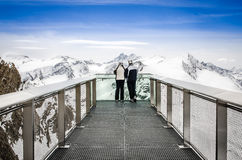 Two people looking at Alps mountains from viewpoint platform Royalty Free Stock Image