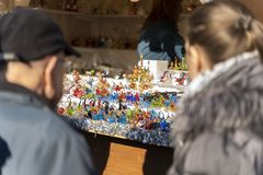 Two people looking on colorful glass figures on a christmas market booth in merano, south tyrol in italy during daylight royalty free stock photography
