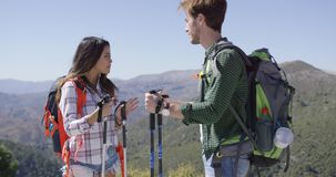 Two people looking at each other. Young couple wearing backpacks standing with trekking poles in hands and looking at each other in mountains stock footage