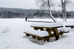 Two people looking at the landscape. Wood bench and table covered of snow in front of a frozen lake Royalty Free Stock Photo