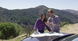 Two people looking at map searching route. Two young people investigating map on car hood using hand glass with beautiful mountains on background stock footage