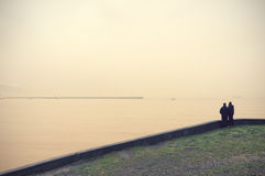Two people looking sea with vintage filter effect Royalty Free Stock Image
