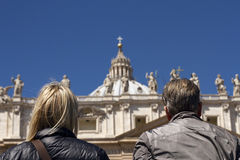 Two people looking at St Pietro basillica in Vatican City. From the point of view of the observers we see the back of the heads framing St Peters Basillca dome stock image