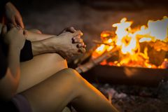Two people in love holding hands, sitting in front of a bond fire. Camping at night. Hawaii campfire. Relaxed and romantic theme Stock Photos