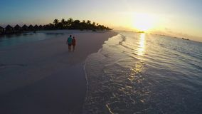 Two people in love during sunset on the tropical beach - aerial stock video