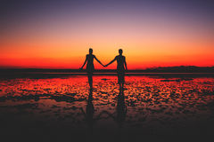 Two people in love walking on the beach. Silhouette of young couple in love holding hands at sunset at the seaside, two people in love walking on the beach Stock Images