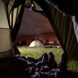Two people lying in tent with view of night camping. Two people lying in tent with a view of night camping, mighty mountains and luminous town. Tourist tents Stock Photos