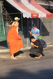 Two people make a merit to monk on the street in the morning while monk`s assitance are waiting. Royalty Free Stock Photography