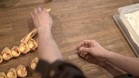 Two people making tortellini traditional Italian food, top view slider shot. Hands of two unrecognizable middle age men making tortellini, a traditional Italian stock footage