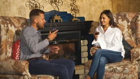 Two people, man and woman in cafe communicate, laughing and enjoying the time spending with each other. Enamored couple sitting in a chair and drinking wine in stock footage