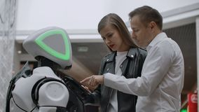 Two people a man and a woman communicate with a robot. Press the robot with your hands on the screen. A robot assistant stock footage