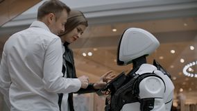Two people a man and a woman communicate with a robot. Press the robot with your hands on the screen. A robot assistant stock video