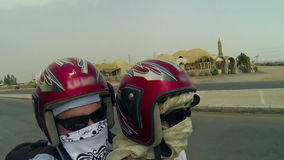 Two people with masks driving on motor in Egypt stock video footage