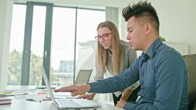 Two People Discussing Ideas Using Laptop. Two people in modern start up office male team leader pointing at screen discussing diverse people group teamwork using stock footage
