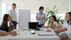 Two people near flipchart offers ideas near business people listens presentation. In conference room stock video footage