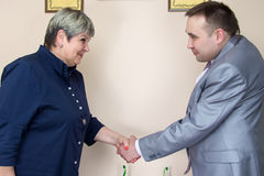 Two people in office shaking hands. Photo of people in office Royalty Free Stock Image
