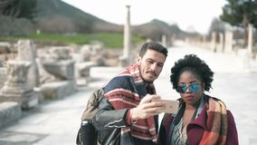 Two people one white man and black woman taking a selfie. Two people one white man and black woman taking a selfie at Ephesus Ancient city in Izmir Selcuk stock video footage
