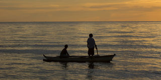 Two People in an outrigger during sunset Royalty Free Stock Images