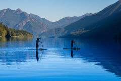 Two people paddleboarding across Crescent Lake in Washington sta. Two people in silhouette paddleboarding across calm Lake Stock Photos