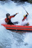 Two people paddling inflatable boat down rapids Royalty Free Stock Photos