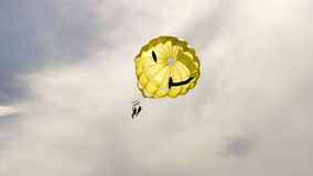 Two people parasailing. Two people up in the air, parasailing under a smiley face chute.  Taken on South Padre Island, Texas Royalty Free Stock Images