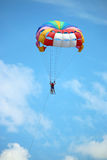 Two people parasailing with parachute on blue sky Stock Image