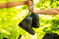 Two people pass boots. Stock Images