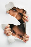 Two people peeking from hole in wall Stock Photo