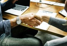 Two People Performing Handshake in Front of Table Stock Photos
