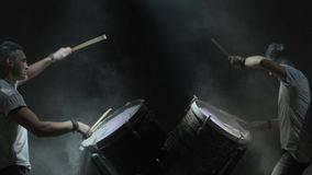 Two people play on color drums on the black background.  stock footage