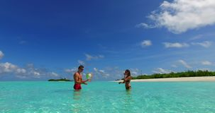 2 people playing ball romantic young couple on a tropical island of white sand beach and blue sky and sea. Two 2 people playing ball romantic young couple on a stock video footage