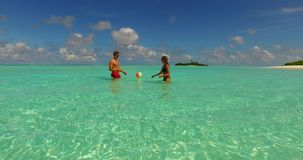 2 people playing ball romantic young couple on a tropical island of white sand beach and blue sky and sea. Two 2 people playing ball romantic young couple on a stock video