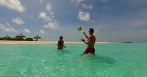 2 people playing ball romantic young couple on a tropical island of white sand beach and blue sky and sea. Two 2 people playing ball romantic young couple on a stock footage