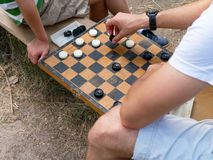Two people playing checkers outside. Close-up on checkers board royalty free stock photography