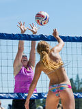 Two people playing at the net in a volleyball game Royalty Free Stock Photo