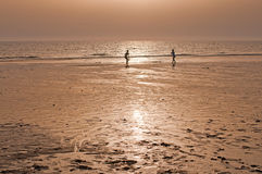 Two people playing tennis on a beach at sunset Royalty Free Stock Image