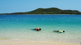 Two people are practicing for snorkeling in the Ocean. They`re wearing life jacket and mask. It is holiday in Samae San Island, Chonburi province, Thailand royalty free stock photos