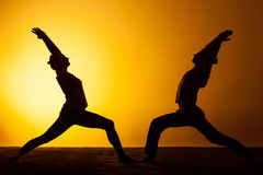 Two people practicing yoga in the sunset light Stock Images