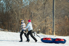 Two People Pull a Big Snow Tube. Family Vacation Snow Tubing Spo Royalty Free Stock Image