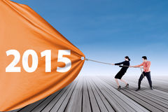 Two people pulling number of 2015 Stock Image