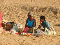 Two people of Puri beach in India. Adult and child sat on Puri beach in Orissa, India Stock Photos