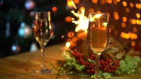 A man and a woman raise glasses of sparkling champagne over a festive table. Two people put glasses of sparkling champagne on the dining table with bengal stock video footage