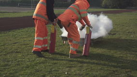 Two people putting out a fire with fire extinguishers. Fire safety education.Two people are running a fire drill, putting out a fire with  compressed carbon stock video footage