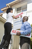Two people putting up notice outside house Stock Photos