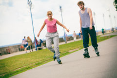 Two people race together riding rollerblades. Stock Photo