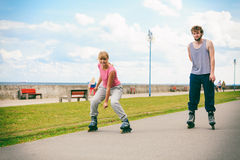 Two people race together riding rollerblades. Royalty Free Stock Photography