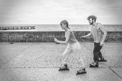 Two people race together riding rollerblades. Stock Image