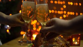 A man and a woman raise glasses of sparkling champagne over a festive table. Two people raise glasses of sparkling champagne,toasting and clinking at a stock video footage