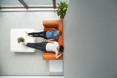 Two People Reclining On Orange Sofa At Office Royalty Free Stock Photo
