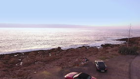 Two people relax near the ocean after traveling on cars. Beautiful girl with man sits on the bench near the ocean. The people are talking. The camera is moving stock video